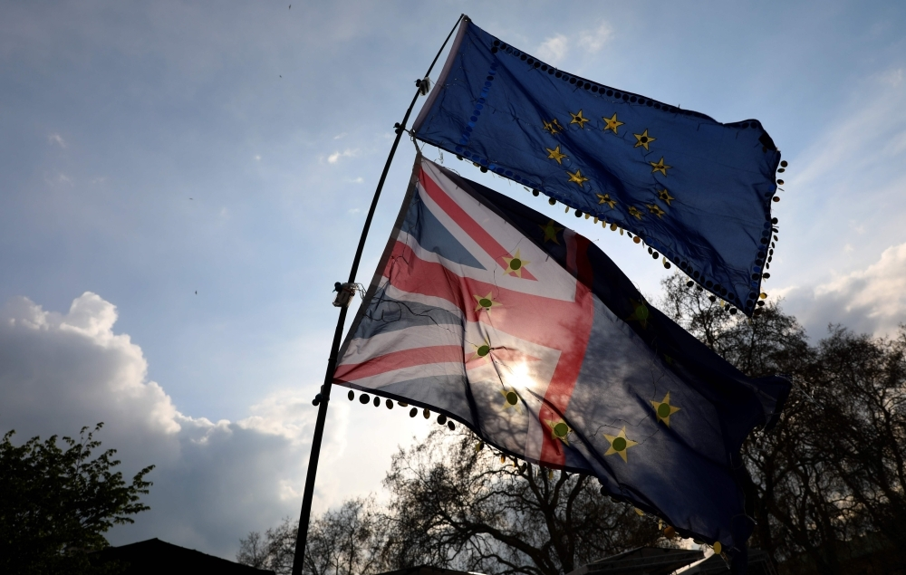 Anti-Brexit activists fly EU and Union flags as they demonstrate near the Houses of Parliament in central London on April 3, 2019. - Prime Minister Theresa May met Wednesday with Britain's opposition leader in a bid to forge a Brexit compromise that avoids a potentially chaotic
