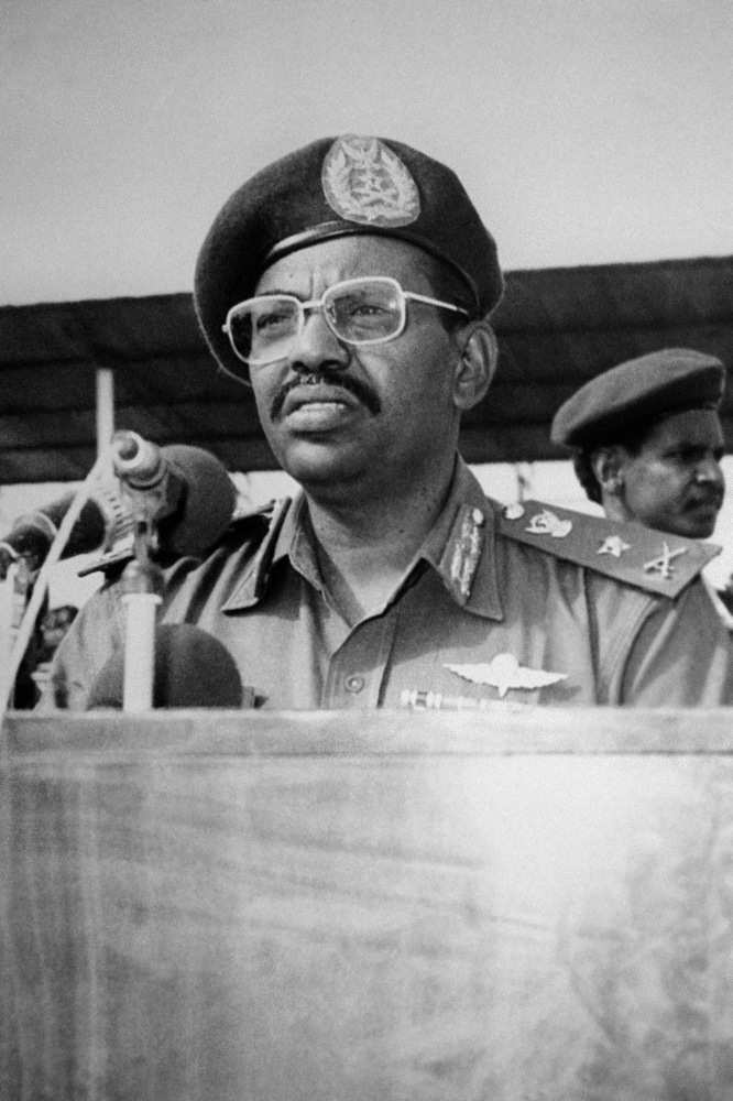 (FILES) In this file photo taken on July 7, 1989, Revolutionary Council ruler and military coup leader General Omar al-Bashir (C) addresses other Revolutionary Council military officers during a graduation ceremony at the Sudanese Military Academy. - Sudanese leader Omar al-Bashir, long wanted on genocide and war crimes charges, was finally brought down in a popular uprising by the very people he ruled with an iron fist for 30 years. One of Africa's longest-serving presidents, the 75-year-old had remained defiant in the face of months-long protests that left dozens of demonstrators dead in clashes with security forces. (Photo by - / AFP)