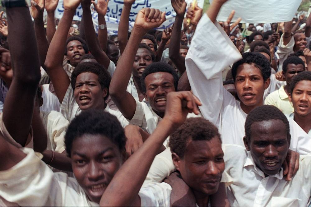 (FILES) In this file photo taken on July 11, 1989, supporters of Revolutionary Council ruler and military coup leader General Omar al-Bashir shout slogans during a pro-government rally in the Sudanese capital Khartoum, as Bashir took power after toppling the civilian government of Prime minister Sadiq Al-Mahdi in a coup on June 30, 1989. - Bashir was ousted on April 11, 2019 by the army after three decades of iron-fisted rule, but protestors swiftly rejected what they denounced as a coup by the regime and vowed to keep up their demonstrations. (Photo by MIKE NELSON / AFP)