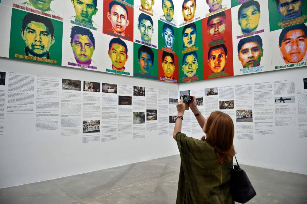 A woman taks a picture of Chinese contemporary artist and activist Ai Weiwei's new exhibition at the University Museum of Contemporary Art (MUAC) in Mexico City on April 11, 2019. - Ai Weiwei unveiled the portraits of the 43 Mexican missing students of Ayotzinapa made with one million Lego pieces. (Photo by ALFREDO ESTRELLA / AFP)