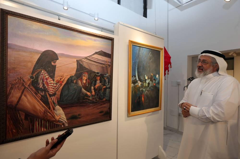 هشام بنجابي الفنان التشكيلي أمام أحد لوحاته (تصوير:علي حميدة)