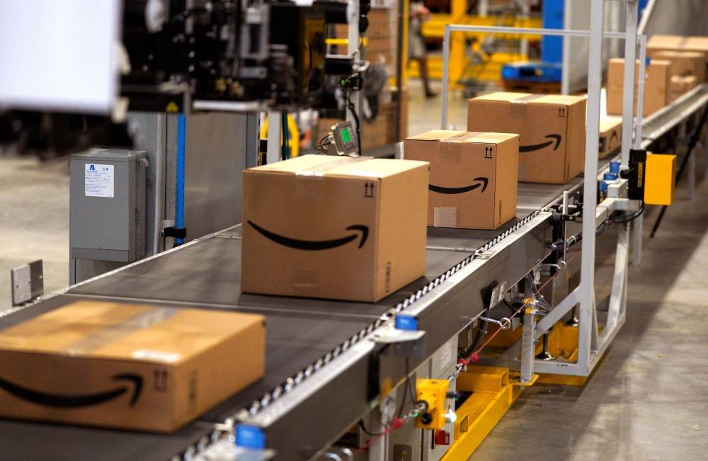 (FILES) In this file photo taken on May 02, 2018, packed orders move down a converyor belt at the Amazon fullfillment center in Aurora, Colorado. - Amazon said Monday, May 13, 2019 it was offering employees $10,000 to quit their jobs and become independent package delivery entrepreneurs for the online retail colossus. An Amazon statement said the latest incentive would also include three months of wages for employees who want to start their own delivery enterprise, and that they would be assured