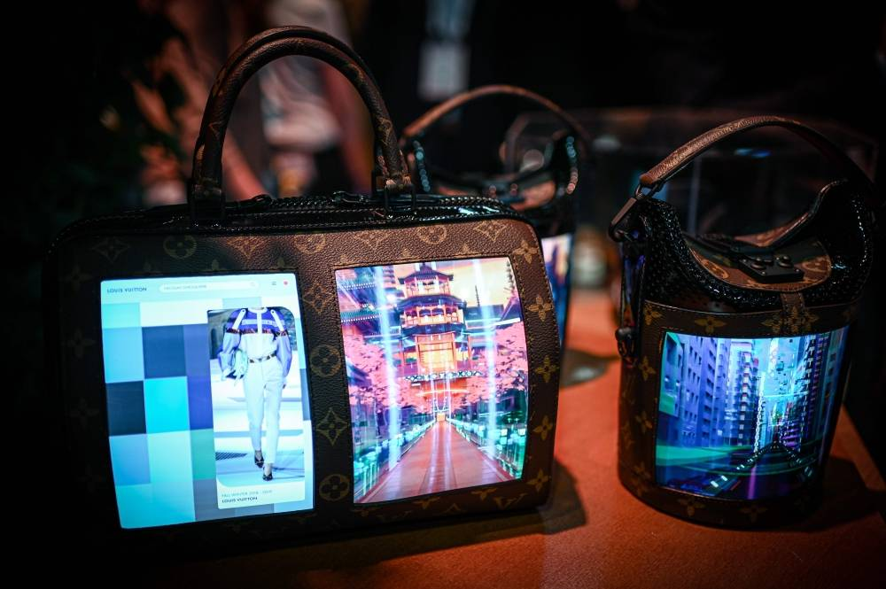 A Louis Vuitton bag with a flexible lcd screen is displayed during the Vivatech startups and innovation fair, in Paris on May 17, 2019. (Photo by Philippe LOPEZ / AFP)