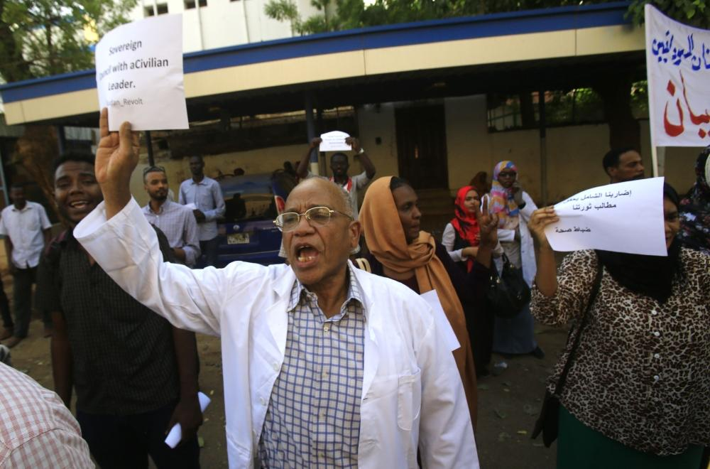 A Sudanese health worker carries a placard as scores of medics hold a rally in front of a hospital in the capital Khartoum on May 23, 2019. - Sudan's protest leaders said today they will seek advice from demonstrators camped outside the army headquarters on how to break a deadlock in talks with the military on installing civilian rule. Medics along with engineers and teachers played a key role in nationwide protests against Omar al-Bashir's rule by forming the Sudanese Professionals Association, the group that initially launched the anti-Bashir campaign. (Photo by ASHRAF SHAZLY / AFP)