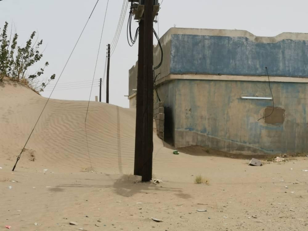 منزل محاط بالرمال بعتود. (تصوير :محمد الحسين)