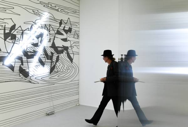 15 August 2019, Berlin: A man walks by artworks of the artist Flaka Haliti in the exhibition of the