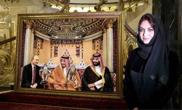 التشكيلية نبيلة أبو الجدايل بجانب إحدى لوحاتها