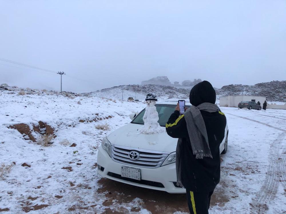 أحد المنتزهين يصنع رجل الثلج على سيارته  (تصوير: عبدالمجيد العجلان)