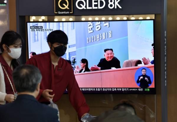 أناس يمرون أمام شاشة إخبارية تليفزيونية تظهر صورة الزعيم الكوري الشمالي كيم جونج أون وهو يحضر احتفالًا بمناسبة الانتهاء من مصنع سمادون للأسمدة الفوسفاتية (أ ف ب)