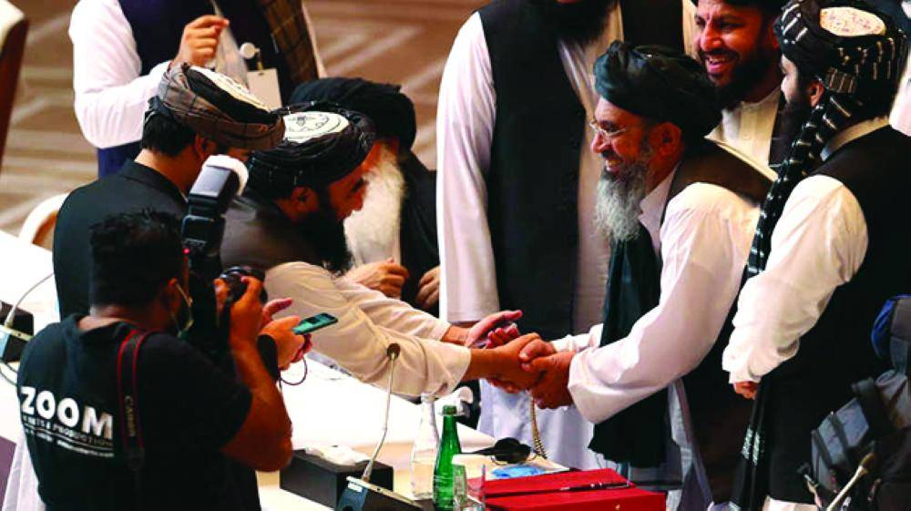 Taliban delegates shake hands during talks between the Afghan government and Taliban insurgents in Doha, Qatar September 12, 2020. REUTERS/Ibraheem al Omari