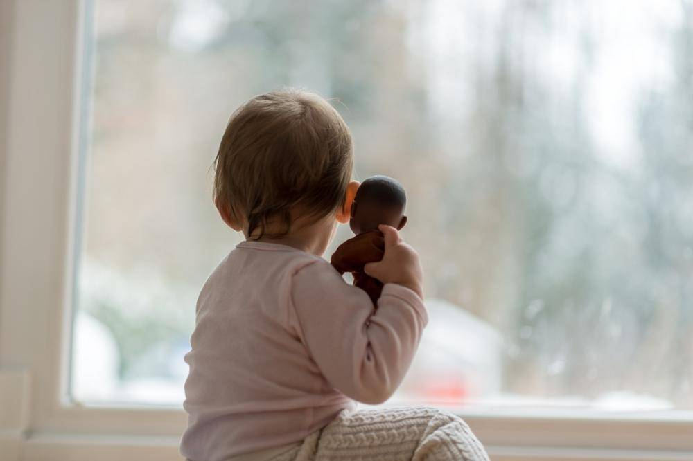 Little baby girl hugging a toy watching the winter snow outdoors as she sits in front of a large view window.