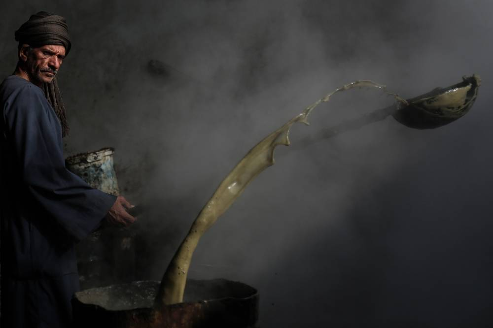FILED - 01 March 2021, Egypt, Mallawi: A worker stirs sugarcane molasses, known locally as