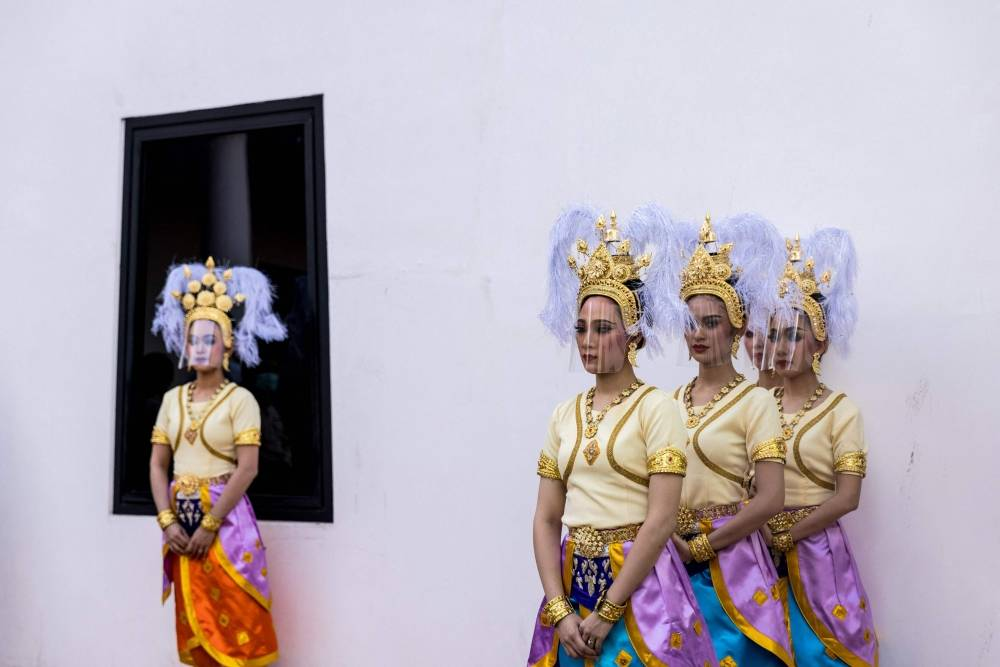 A traditional Thai dancers wears a plastic face shield during an event to mark the return of two ancient sandstone lintels, sacred late 10th or 11th century sandstone support beams, at the Bangkok National Museum in Bangkok on May 31, 2021. (Photo by Jack TAYLOR / AFP)