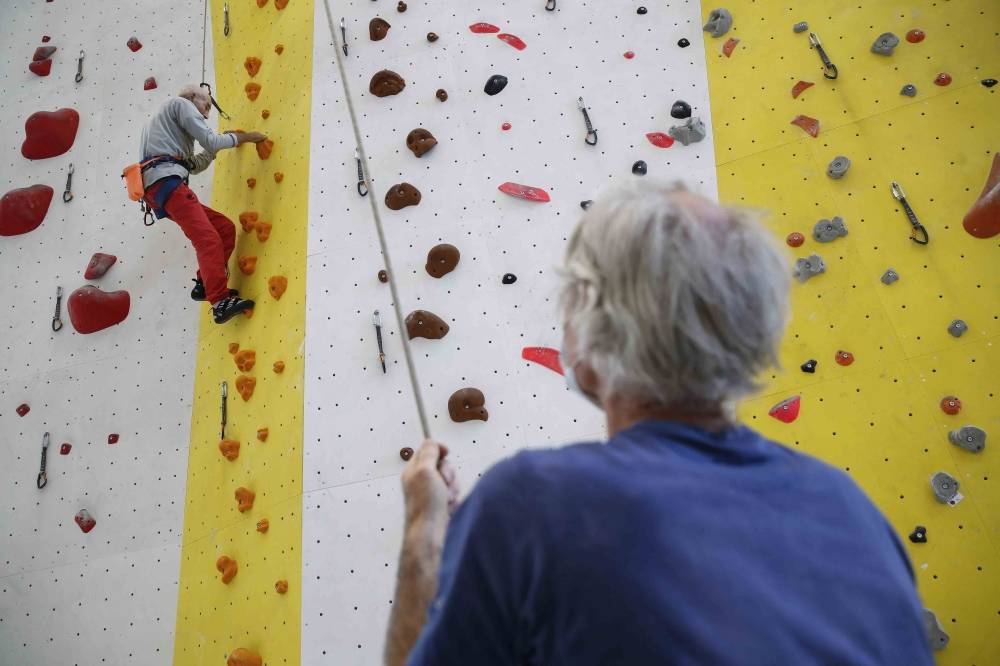Swiss 98-years-old veteran Alpinists Marcel Remy progresses on a wall as his son Claude holds the rope at the indoor climbing centre in Villeneuve on the eastern shores of Lake Geneva, on May 31, 2021. - Climbing has always been major part of Remy's life. Brought up on tales of the mountains, he never stopped going off to discover the great outdoors and the Alps became his playground. Though he mostly climbs indoors these days, Remy still does sorties into the mountains. In 2017, at the age of 94, he conquered the Miroir de l'Argentine, a Swiss climbing classic with its 500 metres of limestone wall. And he shows no sign of stopping. (Photo by STEFAN WERMUTH / AFP)
