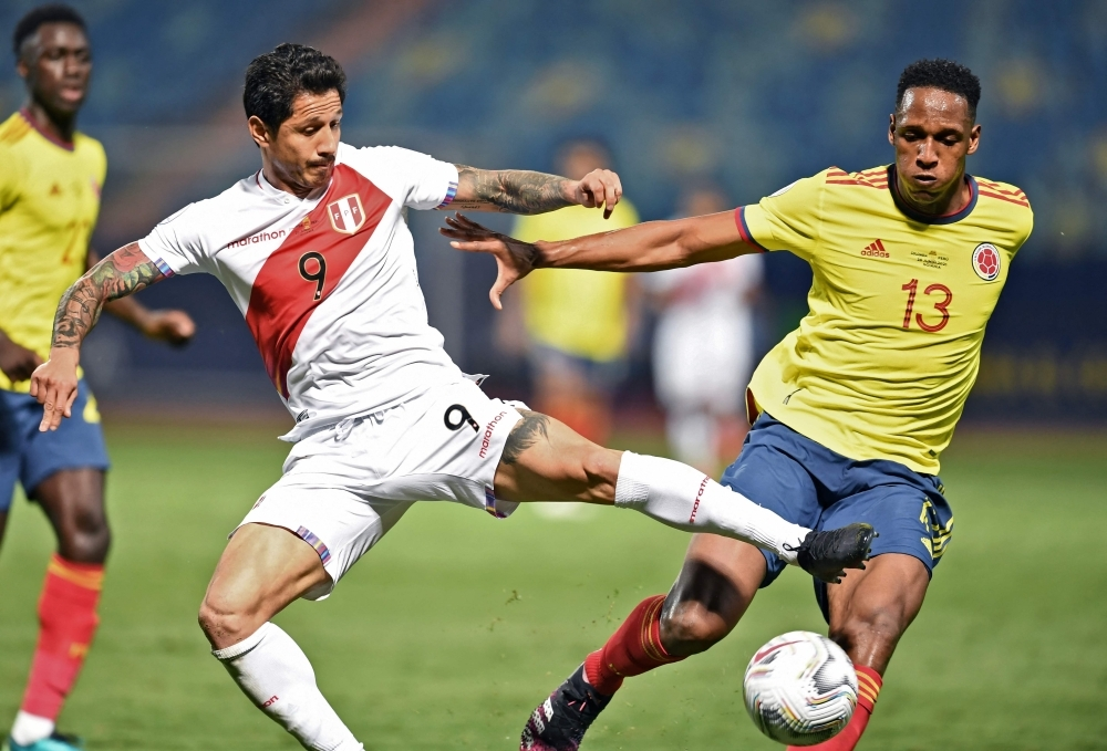 TOPSHOT - Peru's Gianluca Lapadula (L) and Colombia's Yerry Mina vie for the ball during their Conmebol Copa America 2021 football tournament group phase match at the Olympic Stadium in Goiania, Brazil, on June 20, 2021. (Photo by EVARISTO SA / AFP)