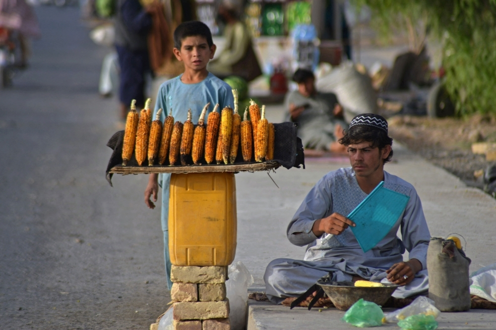 A vendor (R) selling corns waits for customers along the roadside in Kandahar on October 2, 2021. (Photo by Javed TANVEER / AFP)
