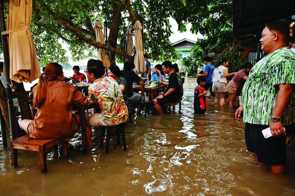 رواد مطعم يحجزون في مطعم تايلاندي لتناول الطعام بين مياه الفيضان
